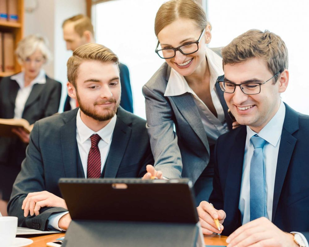 Lawyers in their law firm working on computer with books in background