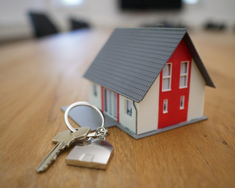 new house keys next to a model house